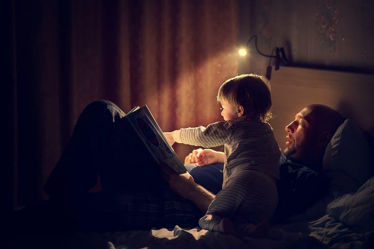 Un homme et un enfant lisent un livre, assis sur un lit